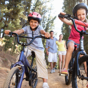 Family on country walk with children riding bikes wearing safety helmets